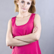 Beautiful young blond woman in a bright pink blouse on a gray background — Stock Photo #40487219