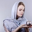Beautiful young woman wrapped in a blue scarf holding a beautiful candle on gray background — Stock Photo #41420731