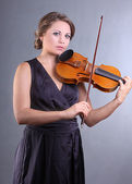 A charming young girl playing the violin professionally — Stock Photo