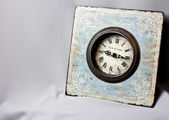 Blue clock in the style of Provence on the gray fabric. Vintage watches. yellow candle — Stock Photo