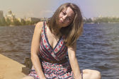 Beautiful young woman basking in the sun near the water — Foto de Stock