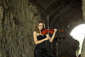 Beautiful curvaceous woman with violin in darkness — Stock Photo