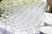 Wedding glasses on the white silk tablecloth, on the street. sunny weather. wedding preparations. — Stock Photo