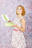 Charmig ung flicka håller en presentförpackning. ljusa olja bakgrund. frisyr. rött kort hår — Stockfoto