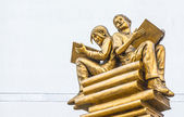Statue boy and girl sitting on book — Stock fotografie
