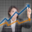 Closeup of young Asian business woman drawing graph — Stockfoto