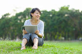 Woman holding tablet in park — Stockfoto
