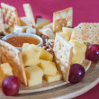 Different varieties of cheese with grapes, crackers, nuts and ho — Stock Photo #42723439