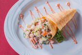 Salad in a waffle cone sauce and greens on a round white plate — Foto Stock