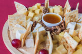 Slices of cheese with grapes, crackers, walnut and honey on a cr — Stockfoto