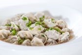 Meat dumplings with greens on a white background in a white plat — Zdjęcie stockowe