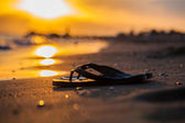 Sandals on the seashore and sunset — Stock Photo