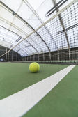 Tennis ball in indoor tennis court — Stock Photo