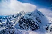 Niesamowite widok z lotu ptaka mount mckinley, lub denali, śnieg i chmury dmuchanie w ciężkich wiatry na szczyt. alaska. — Zdjęcie stockowe