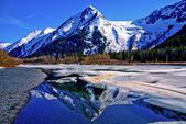 Partially Frozen Lake with Mountain Range Reflected in the Great Alaskan Wilderness. — Stock Photo