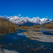 Stock Photo: Azure Sky, Glacial Emerald River, and Snow Capped Mountains with Small AlaskSettlement