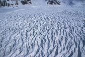 アラスカ山を滑り落ちるひび割れや crevassed の氷河の空撮. — ストック写真