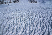 Aerial View of a Cracked and Crevassed Glacier sliding down an Alaskan Mountain. — Stock Photo