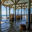 Unusual View of Wooden and Older Concrete Piers Underneath Galveston Beach Structure with Pleasure Pier Carnival on Other Side. — Стоковая фотография