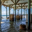 Unusual View of Wooden and Older Concrete Piers Underneath Galveston Beach Structure with Pleasure Pier Carnival on Other Side. — Photo