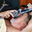 Senior Adult Man adjusting CPAP headgear in Bed — Stock Photo