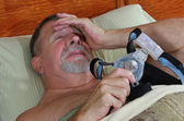 Senior Adult Man frustrated with his CPAP in Bed — Stock Photo