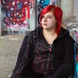 Redhead girl with piercing on graffiti background — Stock Photo #27169643