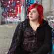 Redhead girl with piercing on graffiti background — Stock Photo