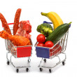 Meat and vegetables in two shopping carts, isolated on white  — Stock Photo