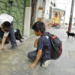 Peruvian school boys play with coins on a street in Iquitos, Peru. — Stockfoto