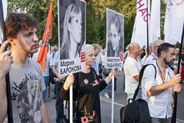 People hold posters with portraits of political prisoners at a meeting in Moscow, Russia.