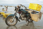 Old motorcycle made in Soviet Union waits loading on the beach in Mui Ne, Vietnam. — Stock Photo