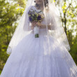 The bride is closed veil with a bouquet in hand — Stock Photo
