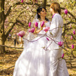 Newlyweds on nature background with blossoming magnolias — Foto Stock