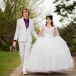 Stock Photo: Happy bride and groom in shady alley on wedding walk
