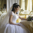 Happy young bride with wedding bouquet — Stock Photo