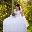 Portrait of a beautiful bride in white wedding dress sitting on  — Stock Photo