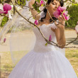 Young happy bride smells flowers magnolia outdoors — Stock Photo