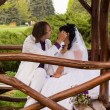 Couple in love bride and groom posing sitting on wooden bench in — Stock Photo