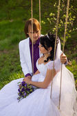 Bride and groom swinging on a swing — Fotografia Stock