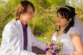 Romantic wedding couple sitting on a bench in the park — Stock Photo
