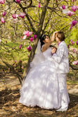 Newlyweds on nature background with blossoming magnolias — Stock Photo