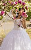 Joven novia feliz huele magnolia flores al aire libre — Foto de Stock