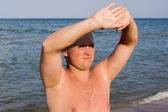 Nice guy squinting in the sun on beach — Stock Photo