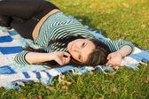 Young woman laying down on the ground in autumn park — Stok fotoğraf