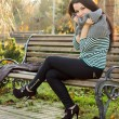Girl sitting on bench outdoors — Stock Photo