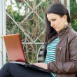 Young beautiful brunette student in profile sits on bench about — Stock Photo
