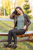 Girl sitting on bench outdoors — Stockfoto