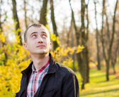 Young handsome man in autumn park — Stock Photo