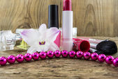 Cosmetics and flowers on table on wooden background — Stock Photo